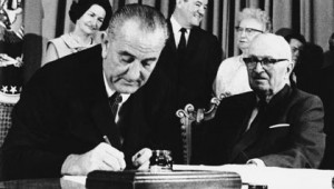 President Johnson signs Medicare and Medicaid into law on July 30, 1965. At his right is Arkansas Dixiecrat Wilbur Mills, originally one of Medicare and Medicaid's chief opponents.